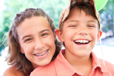 A young girl with braces from Dougherty Orthodontics smiling with a young boy in Sherman Oaks, CA.